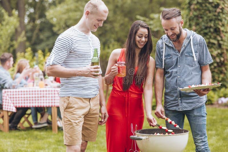 Усмехаясь друзья жаря shashliks и выпивая пиво во время приём гостей в саду стоковое изображение rf