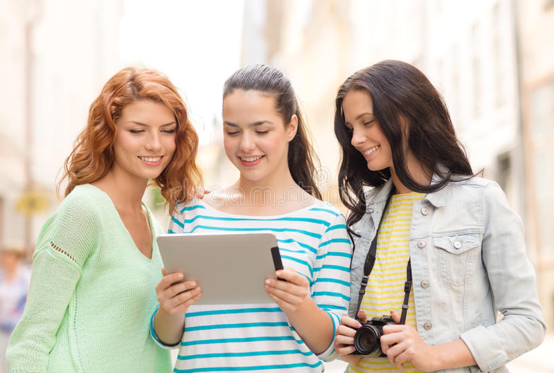 Усмехаясь девочка-подростки с ПК и камерой таблетки стоковое фото