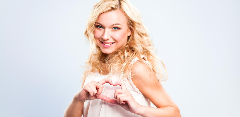 Усмехаясь девушка в белых рубашках показывая сердце с руками стоковая фотография