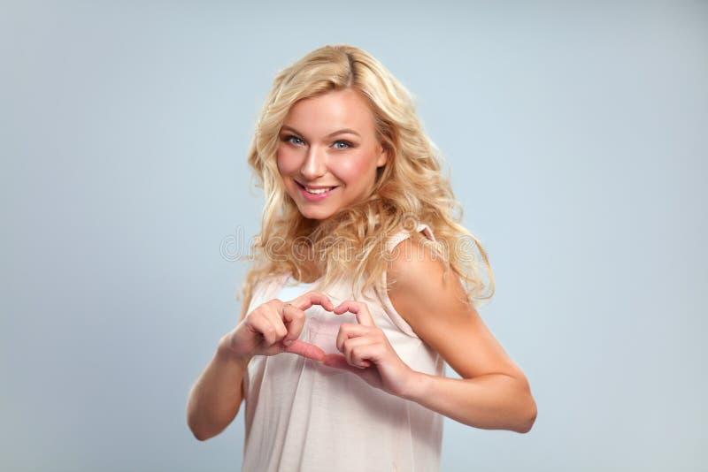 Усмехаясь девушка в белых рубашках показывая сердце с руками стоковая фотография rf