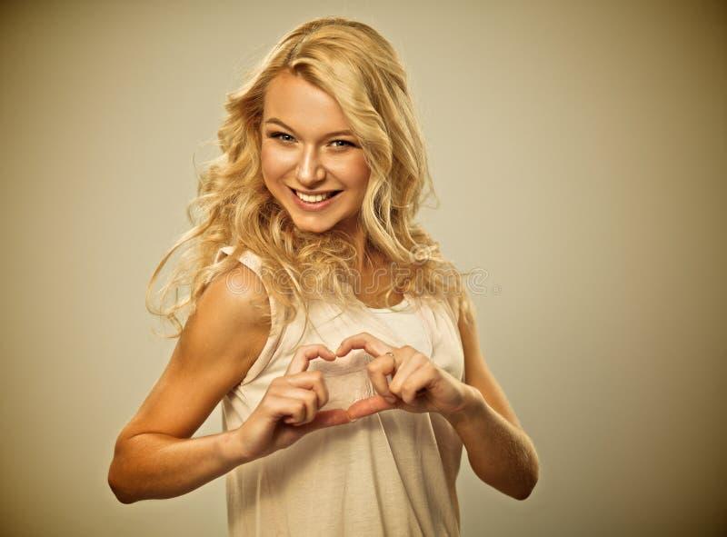 Усмехаясь девушка в белых рубашках показывая сердце с стоковое фото