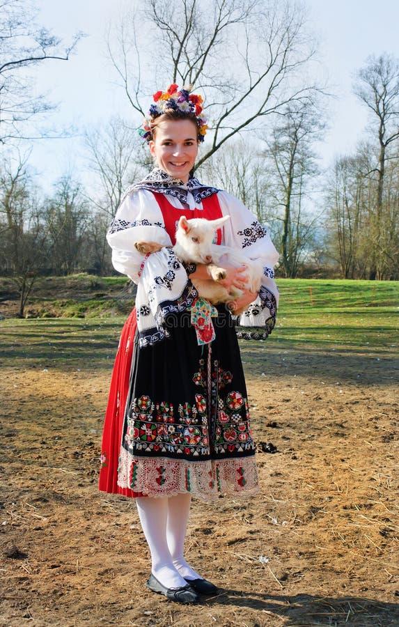 Усмехаясь девушка в костюме людей с маленькой овечкой стоковое фото