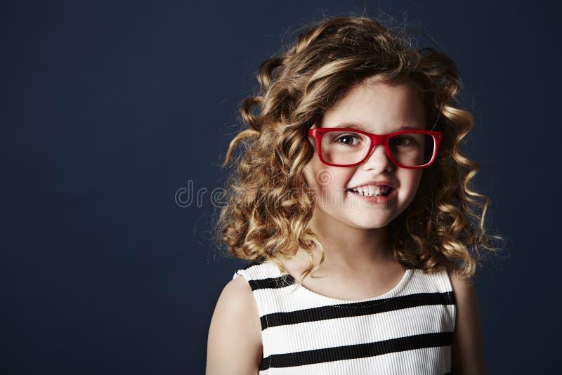 Усмехаясь девушка в красных зрелищах стоковые изображения