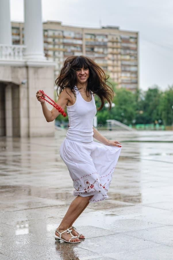 Усмехаясь девушка в предпосылке города дождя стоковые фотографии rf