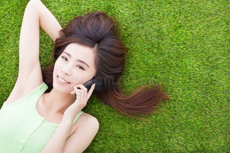 Download Усмехаясь девушка лежа вниз на луге и говорить Стоковое Фото - изображение насчитывающей контакт, жизнерадостно: 40588638