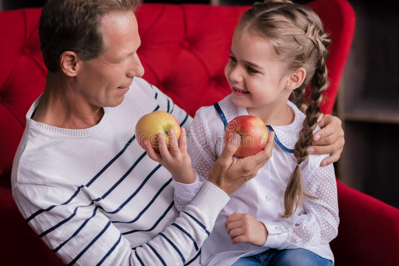 Усмехаясь девушка держа 2 яблока с ее дедом стоковое фото rf