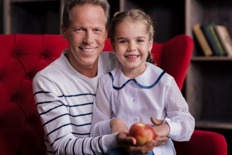 Усмехаясь девушка держа яблоко с ее дедом стоковое фото rf