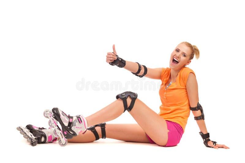 Усмехаясь девушка кататься на коньках ролика показывая большой палец руки вверх. стоковые изображения rf