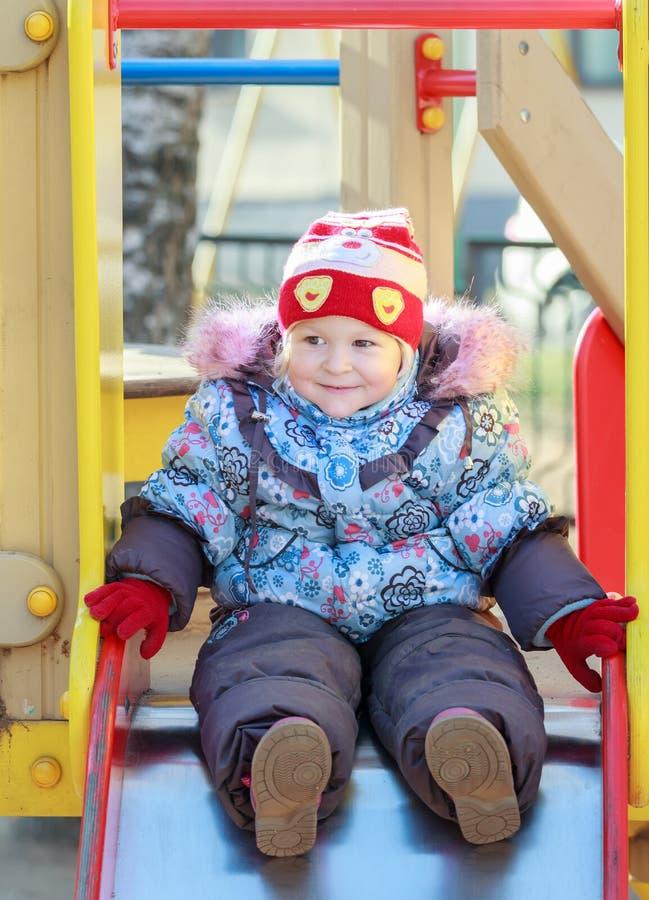 Усмехаясь девушка малыша нося теплые одежды осени стоковое фото