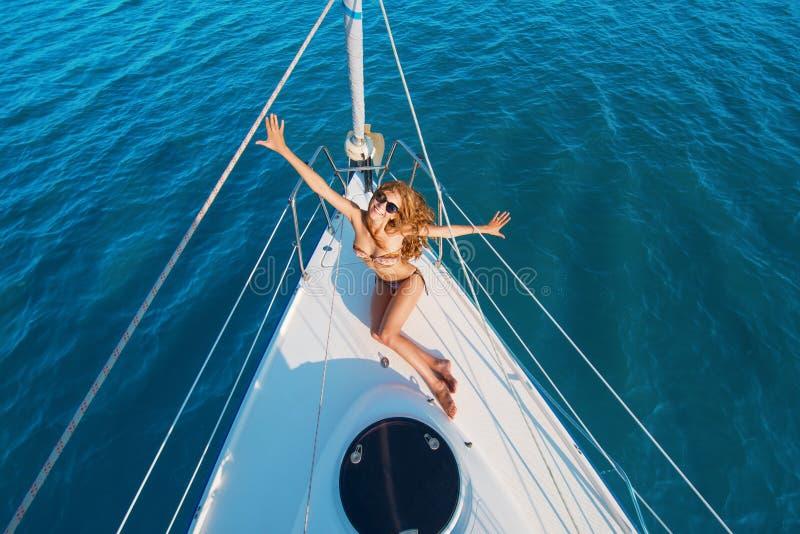 Усмехаясь девушка на белой яхте стоковые изображения rf