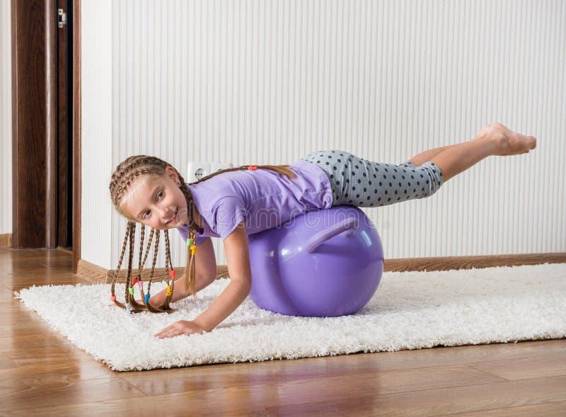 Усмехаясь девушка на шарике стоковая фотография rf