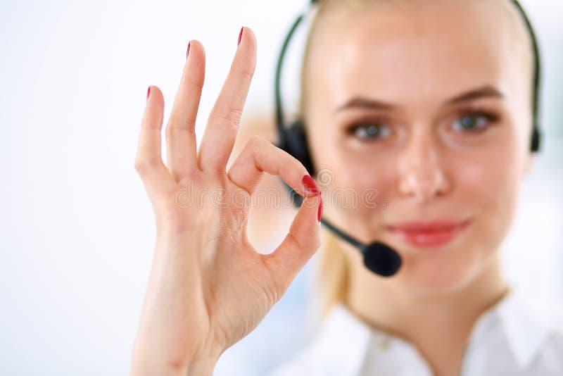 Усмехаясь девушка обслуживания клиента показывая о'кеы, изолированный стоковое изображение rf