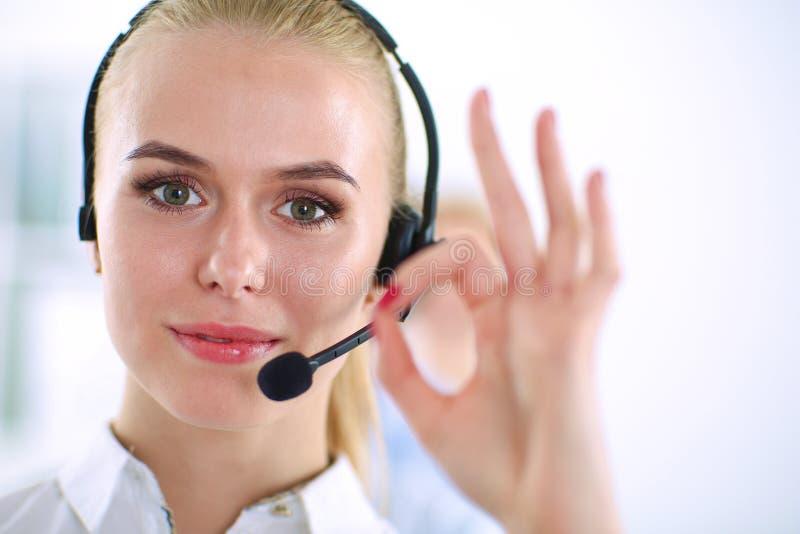 Усмехаясь девушка обслуживания клиента показывая о'кеы, стоковые фото