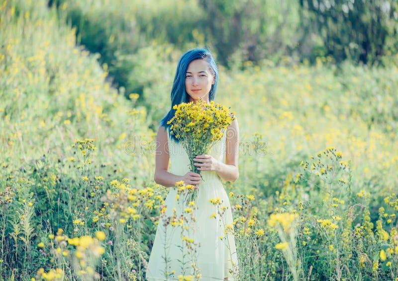 Усмехаясь девушка отдыхая в поле лета стоковые изображения rf