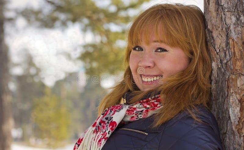 Усмехаясь девушка полагается против хобота сосны closeup стоковые изображения rf