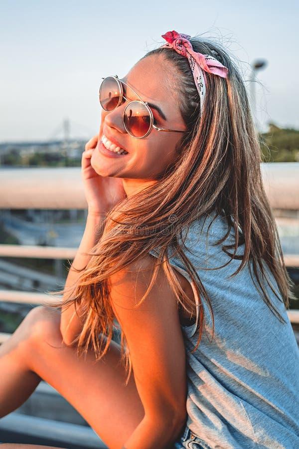 Усмехаясь девушка представляя на мосте стоковая фотография