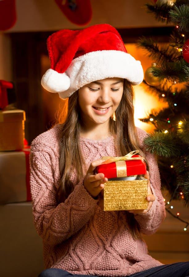 Усмехаясь девушка представляя с золотой подарочной коробкой рождества стоковые фото