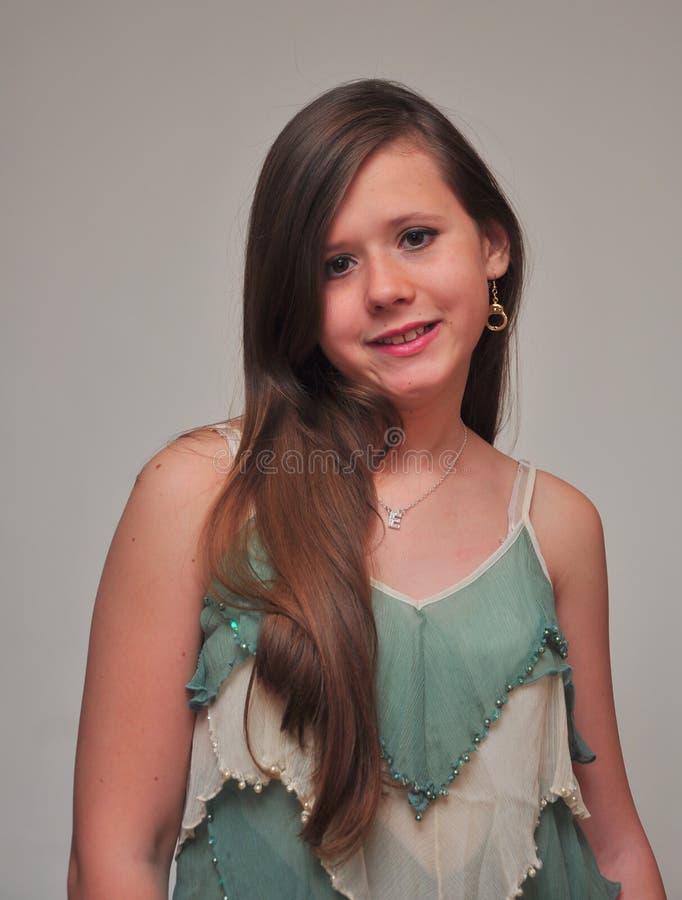 Усмехаясь девушка против белой предпосылки стоковые фотографии rf