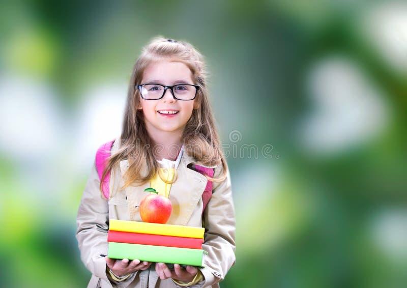 Усмехаясь девушка ребенка с яблоком рюкзака книг задняя школа к стоковые фотографии rf