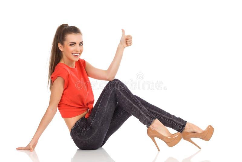 Усмехаясь девушка сидя на поле и показывая большой палец руки вверх стоковая фотография