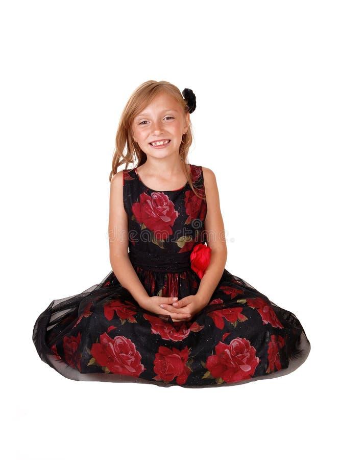 Усмехаясь девушка сидя на поле стоковая фотография rf