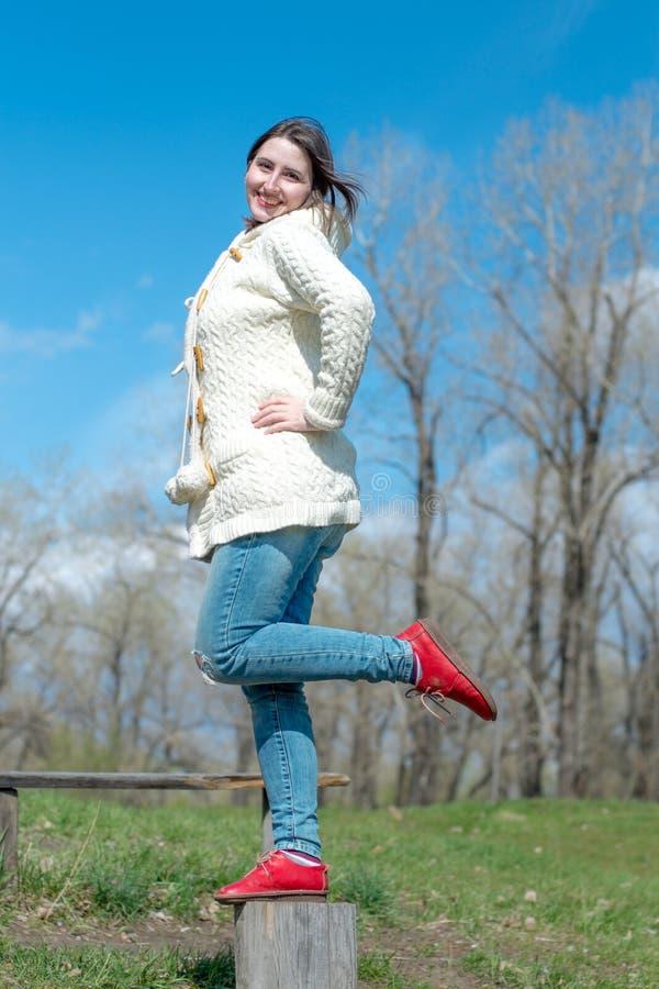 Усмехаясь девушка стоя на пне стоковое изображение rf