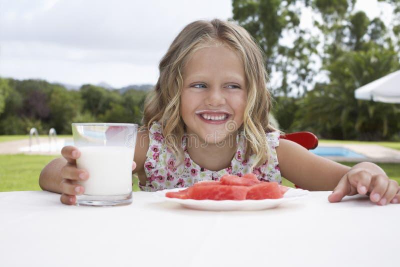 Усмехаясь девушка с арбузом и стеклом молока Outdoors стоковые изображения rf