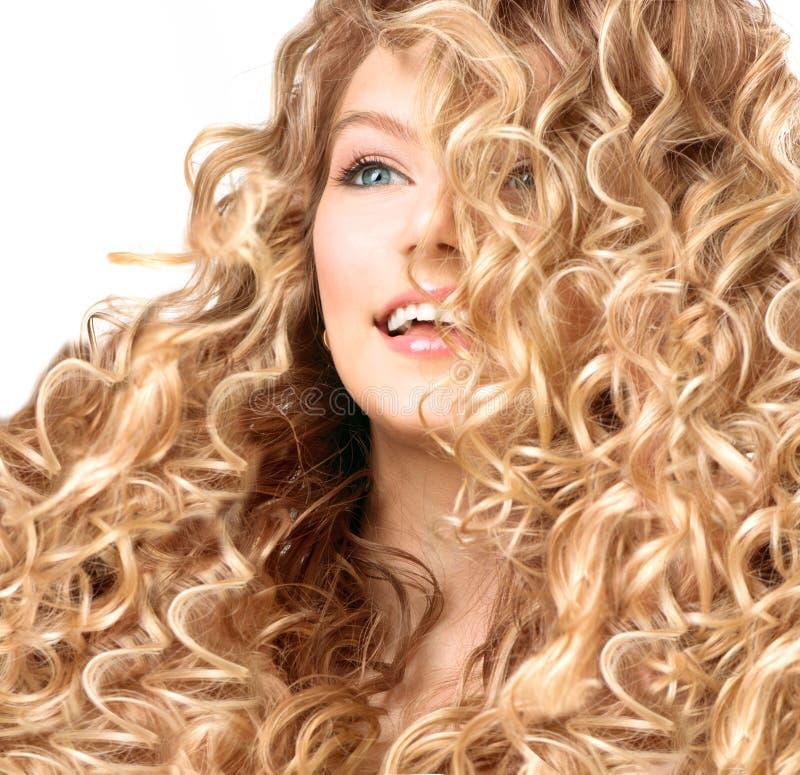 Усмехаясь девушка с волосами permed блондинкой стоковое фото