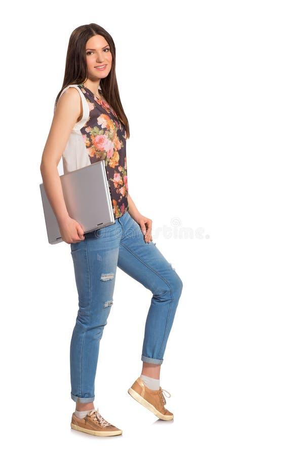 Усмехаясь девушка, с высотой компьтер-книжки полной стоковые фото