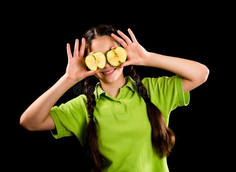 Усмехаясь девушка с зеленым яблоком на глазах стоковые изображения