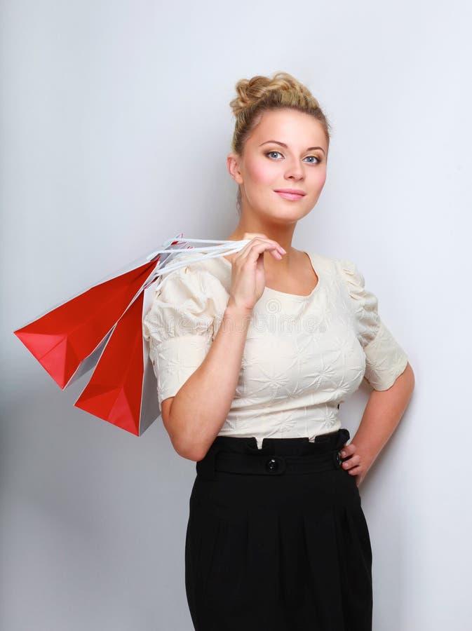 Усмехаясь девушка с хозяйственными сумками в магазине стоковые фотографии rf