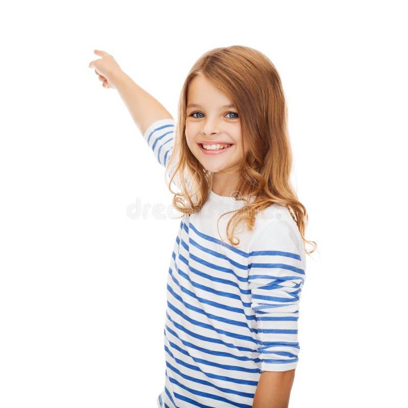 Усмехаясь девушка указывая на виртуальный экран стоковая фотография rf