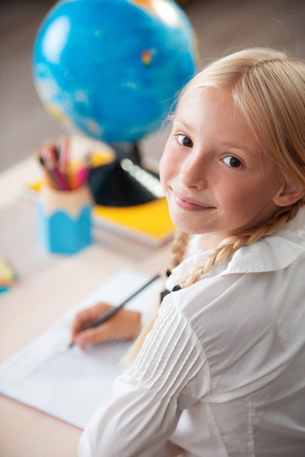 Усмехаясь девушка школы сидя в классе стоковое изображение