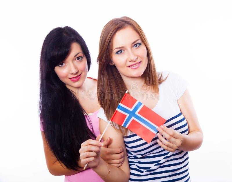 2 усмехаясь девушки держа норвежский флаг. стоковая фотография