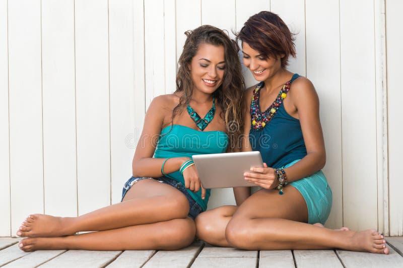 Усмехаясь девушки используя таблетку цифров стоковые изображения rf