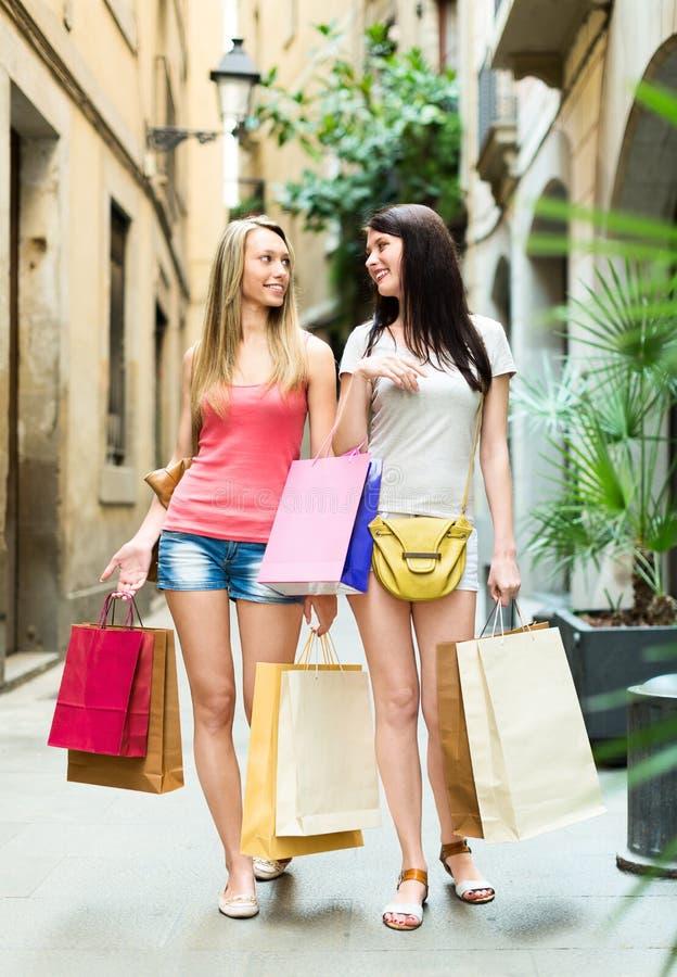 2 усмехаясь девушки идя и обсуждая приобретения стоковые фото