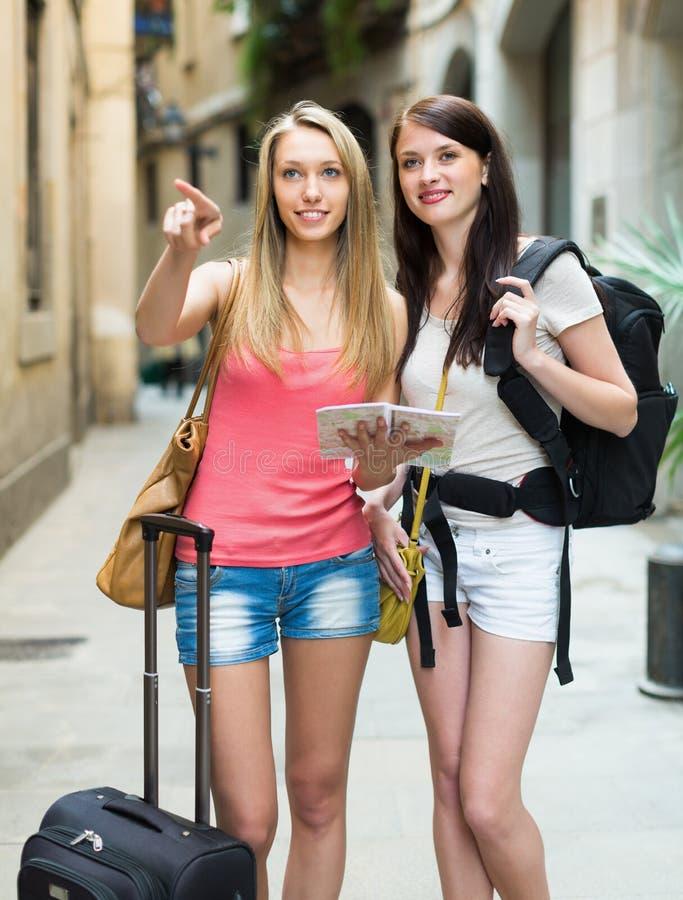 2 усмехаясь девушки с картой стоковое изображение