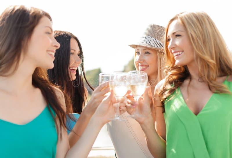 Усмехаясь девушки с стеклами шампанского стоковое фото rf