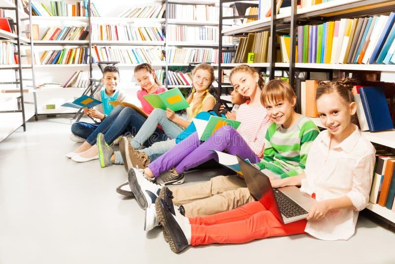 6 усмехаясь детей сидя в ряд на поле стоковая фотография