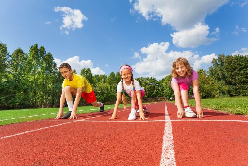Усмехаясь дети в готовом положении, который нужно побежать стоковая фотография