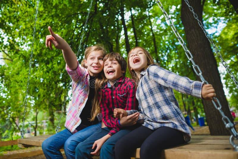 Усмехаясь дети имея потеху на спортивной площадке Дети играя outdoors в лете Подростки ехать на качании снаружи стоковое фото
