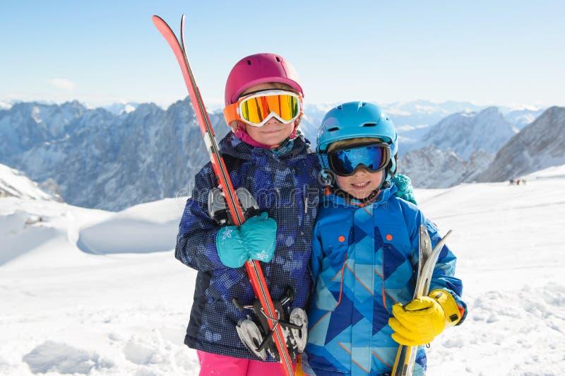 Усмехаясь дети наслаждаясь каникулами зимы в горах стоковое изображение