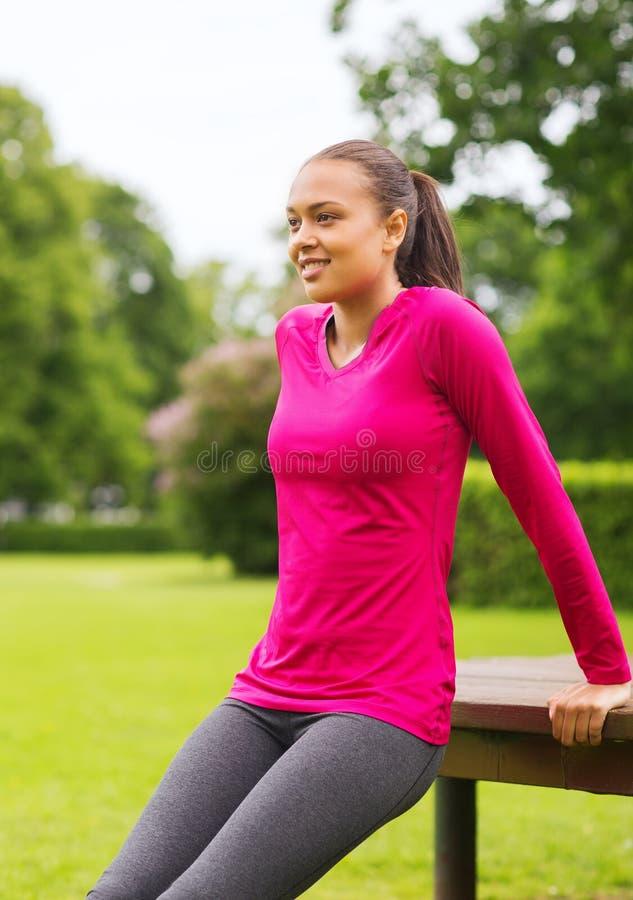 Усмехаясь делать женщины нажим-поднимает на стенде outdoors стоковое фото rf