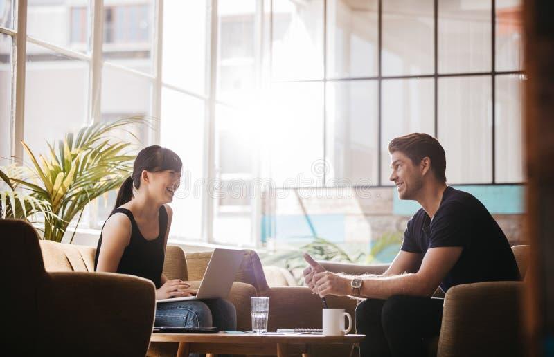 Усмехаясь деловые партнеры работая совместно в современном офисе стоковая фотография rf