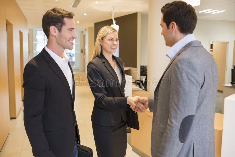 Усмехаясь деловые партнеры тряся руки в зале, лобби стоковые изображения