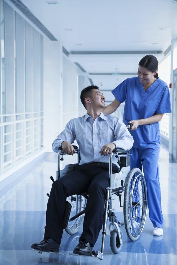 Усмехаясь женская медсестра нажимая и помогая пациента в кресло-коляске в больнице стоковое фото rf