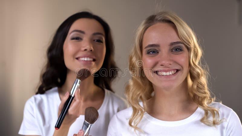 Усмехаясь женские друзья прикладывая макияж перед зеркалом, уроки красоты стоковая фотография rf