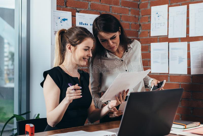 Усмехаясь женские коллеги читая печатные документы сидя в офисе стоковое изображение
