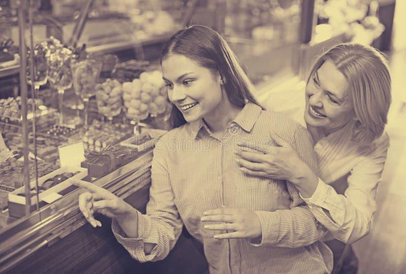 Усмехаясь женские друзья выбирая точные шоколады и confectione стоковая фотография
