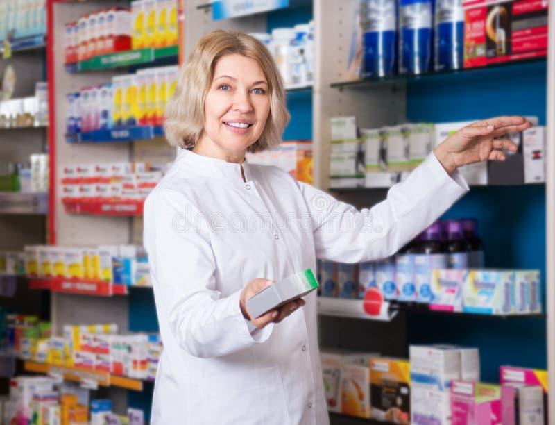 Усмехаясь женский аптекарь в аптеке стоковая фотография rf